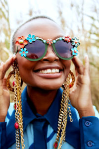 Ozbob Eyewear, Black Model, Field of Grass, Glasses, beads, chain around her neck, earrings, individual smiling.