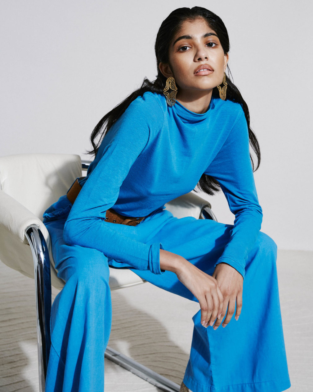 Model wearing blue jumpsuit, seated on chair, Asha Eleven brand, styled by Chrisna de Bruyn. Disco Creatives, Disco Casting, Disco Production. Candice Hatting.